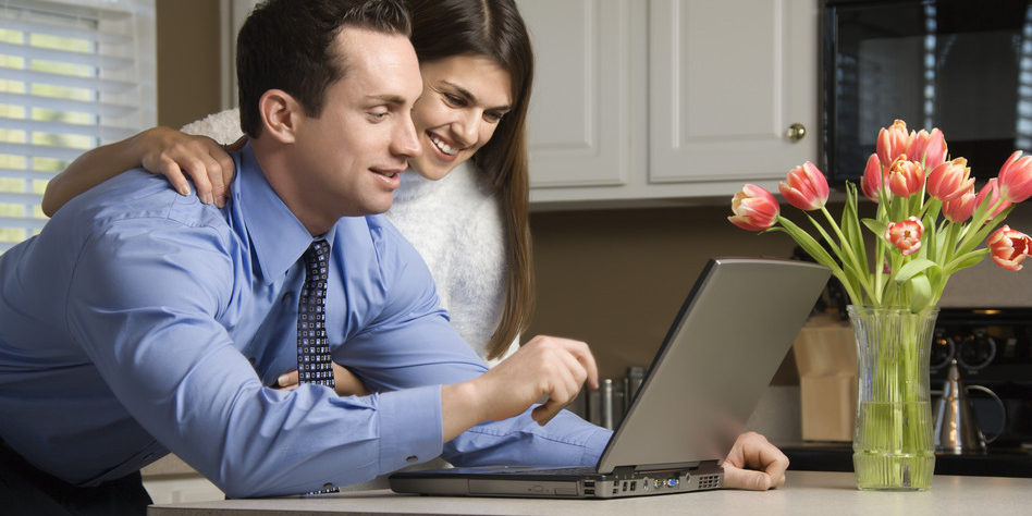 Caucasian couple in kitchen looking at laptop computer.